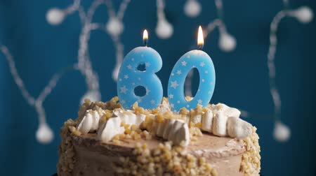 anlamlı : Birthday cake with 60 number burning candle by lighter on blue backgraund. Candles are set on fire. Slow motion and close-up view