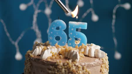 anlamlı : Birthday cake with 65 number burning candle by lighter on blue backgraund. Candles are set on fire. Slow motion and close-up view