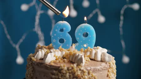 anlamlı : Birthday cake with 69 number burning candle by lighter on blue backgraund. Candles are set on fire. Slow motion and close-up view