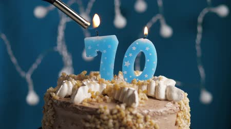 výrazný : Birthday cake with 70 number burning candle by lighter on blue backgraund. Candles are set on fire. Slow motion and close-up view