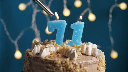 výrazný : Birthday cake with 71 number burning candle by lighter on blue backgraund. Candles are set on fire. Slow motion and close-up view
