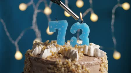 výrazný : Birthday cake with 73 number burning candle by lighter on blue backgraund. Candles are set on fire. Slow motion and close-up view