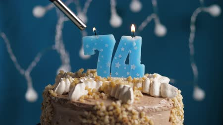 výrazný : Birthday cake with 74 number burning candle by lighter on blue backgraund. Candles are set on fire. Slow motion and close-up view