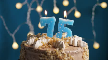 anlamlı : Birthday cake with 75 number burning candle by lighter on blue backgraund. Candles are set on fire. Slow motion and close-up view
