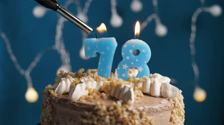 výrazný : Birthday cake with 78 number burning candle by lighter on blue backgraund. Candles are set on fire. Slow motion and close-up view