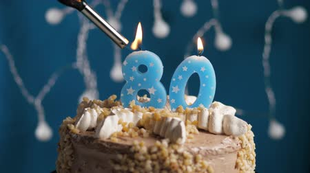 anlamlı : Birthday cake with 80 number burning candle by lighter on blue backgraund. Candles are set on fire. Slow motion and close-up view