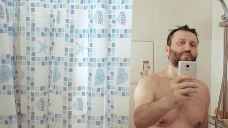 obsession : Bearded man in shower uses Internet in smartphone phone, reads news social networks. Water is pouring on his head. Slow motion