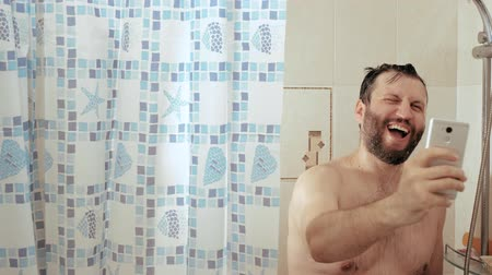 obsession : Bearded man in shower holds telephone in his hands and reads news, he is very happy and laughs. Slow Motion Stock Footage