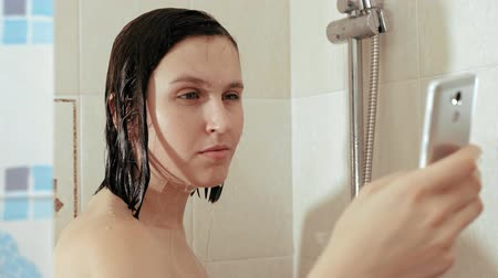 obsession : Girl washes in shower and uses phone. Woman leafs through news of social networks while standing under water that flows down her head. Slow motion and close up Stock Footage