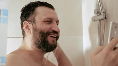 obsession : Man in shower with phone laughs reads looks into smartphone. Internet social network smartphone cell addiction concept. Slow motion and close up