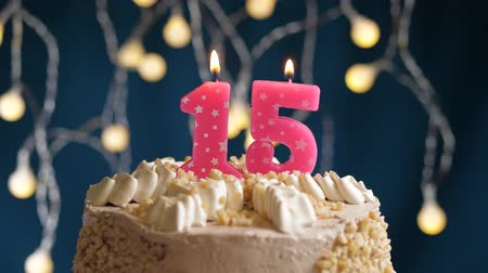 inflar : Birthday cake with 15 number pink burning candle on blue backgraund. Candles blow out. Slow motion and close-up view