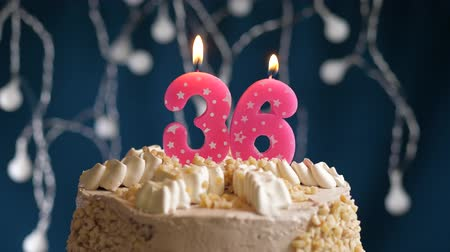 inflar : Birthday cake with 36 number pink burning candle on blue backgraund. Candles blow out. Slow motion and close-up view Archivo de Video