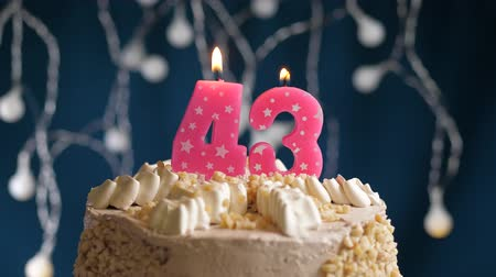 inflar : Birthday cake with 43 number pink burning candle on blue backgraund. Candles blow out. Slow motion and close-up view