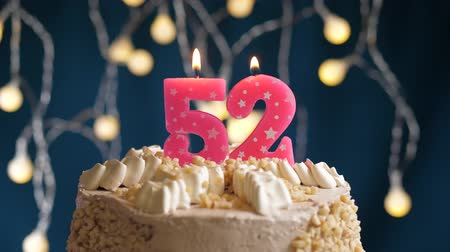 inflar : Birthday cake with 52 number pink burning candle on blue backgraund. Candles blow out. Slow motion and close-up view