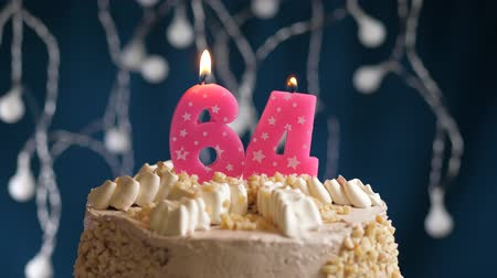 inflar : Birthday cake with 64 number pink burning candle on blue backgraund. Candles blow out. Slow motion and close-up view