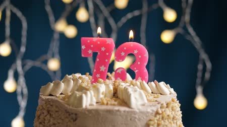 inflar : Birthday cake with 73 number pink burning candle on blue backgraund. Candles blow out. Slow motion and close-up view