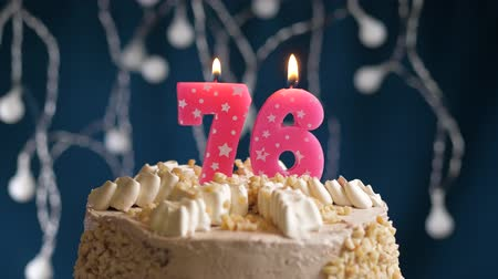 inflar : Birthday cake with 76 number pink burning candle on blue backgraund. Candles blow out. Slow motion and close-up view