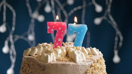 inflar : Birthday cake with 77 number pink burning candle on blue backgraund. Candles blow out. Slow motion and close-up view Archivo de Video