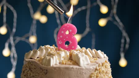 zapalovač : Birthday cake with 6 number burning by lighter pink candle on blue backgraund. Candles are set on fire. Slow motion and close-up view Dostupné videozáznamy
