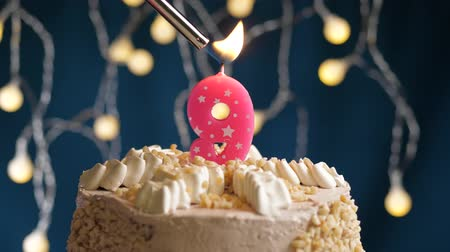 zapalovač : Birthday cake with 9 number burning by lighter pink candle on blue backgraund. Candles are set on fire. Slow motion and close-up view