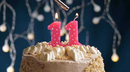 çakmak : Birthday cake with 11 number burning by lighter pink candle on blue backgraund. Candles are set on fire. Slow motion and close-up view