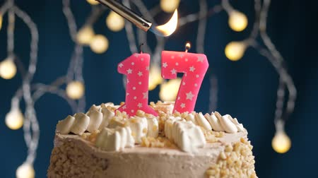 çakmak : Birthday cake with 17 number burning by lighter pink candle on blue backgraund. Candles are set on fire. Slow motion and close-up view