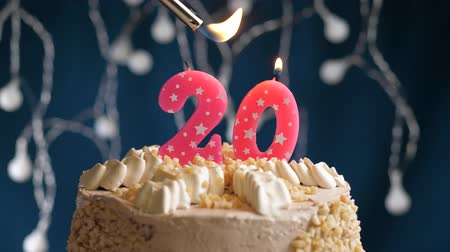 zapalovač : Birthday cake with 20 number burning by lighter pink candle on blue backgraund. Candles are set on fire. Slow motion and close-up view Dostupné videozáznamy