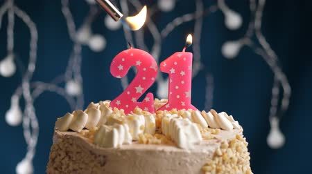 zapalovač : Birthday cake with 21 number burning by lighter pink candle on blue backgraund. Candles are set on fire. Slow motion and close-up view