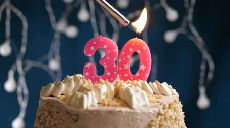 harminc : Birthday cake with 30 number burning by lighter pink candle on blue backgraund. Candles are set on fire. Slow motion and close-up view
