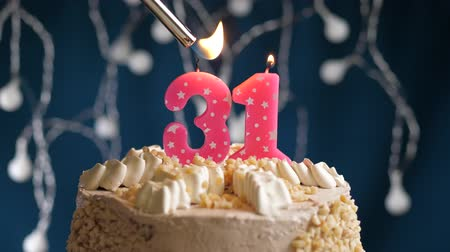zapalovač : Birthday cake with 31 number burning by lighter pink candle on blue backgraund. Candles are set on fire. Slow motion and close-up view Dostupné videozáznamy