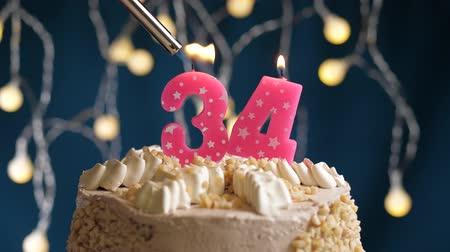 çakmak : Birthday cake with 34 number burning by lighter pink candle on blue backgraund. Candles are set on fire. Slow motion and close-up view