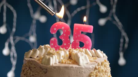zapalovač : Birthday cake with 35 number burning by lighter pink candle on blue backgraund. Candles are set on fire. Slow motion and close-up view
