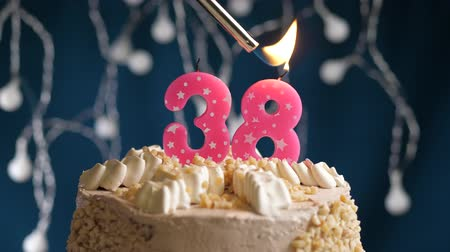 zapalovač : Birthday cake with 38 number burning by lighter pink candle on blue backgraund. Candles are set on fire. Slow motion and close-up view