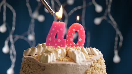zapalovač : Birthday cake with 40 number burning by lighter pink candle on blue backgraund. Candles are set on fire. Slow motion and close-up view Dostupné videozáznamy