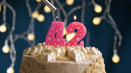 çakmak : Birthday cake with 42 number burning by lighter pink candle on blue backgraund. Candles are set on fire. Slow motion and close-up view