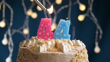 çakmak : Birthday cake with 44 number burning by lighter pink candle on blue backgraund. Candles are set on fire. Slow motion and close-up view Stok Video