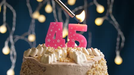 çakmak : Birthday cake with 45 number burning by lighter pink candle on blue backgraund. Candles are set on fire. Slow motion and close-up view Stok Video