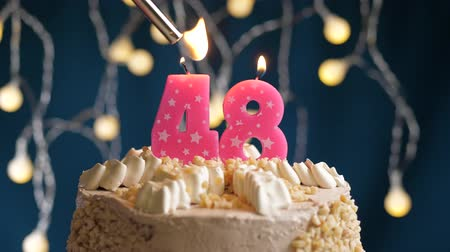 zapalovač : Birthday cake with 48 number burning by lighter pink candle on blue backgraund. Candles are set on fire. Slow motion and close-up view Dostupné videozáznamy