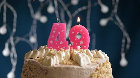 çakmak : Birthday cake with 49 number burning by lighter pink candle on blue backgraund. Candles are set on fire. Slow motion and close-up view
