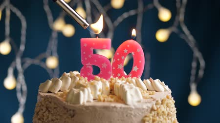 ötvenes : Birthday cake with 50 number burning by lighter pink candle on blue backgraund. Candles are set on fire. Slow motion and close-up view
