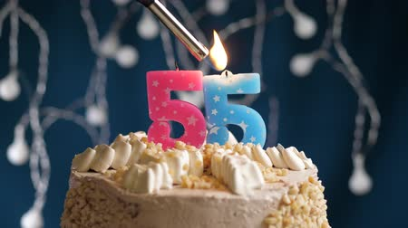 zapalovač : Birthday cake with 55 number burning by lighter pink candle on blue backgraund. Candles are set on fire. Slow motion and close-up view