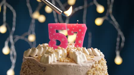 zapalovač : Birthday cake with 57 number burning by lighter pink candle on blue backgraund. Candles are set on fire. Slow motion and close-up view Dostupné videozáznamy