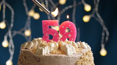 kekler : Birthday cake with 59 number burning by lighter pink candle on blue backgraund. Candles are set on fire. Slow motion and close-up view Stok Video
