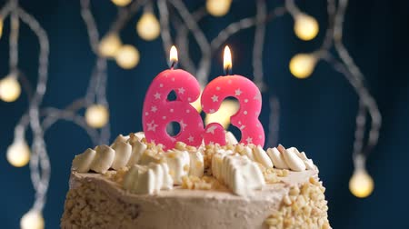 zapalovač : Birthday cake with 63 number burning by lighter pink candle on blue backgraund. Candles are set on fire. Slow motion and close-up view