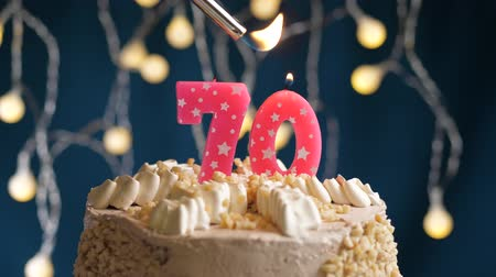 çakmak : Birthday cake with 70 number burning by lighter pink candle on blue backgraund. Candles are set on fire. Slow motion and close-up view