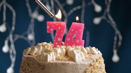 zapalovač : Birthday cake with 74 number burning by lighter pink candle on blue backgraund. Candles are set on fire. Slow motion and close-up view