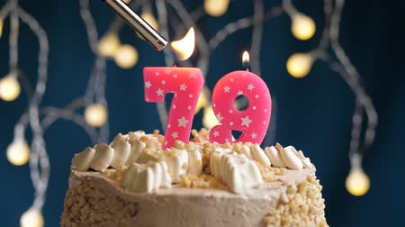 çakmak : Birthday cake with 79 number burning by lighter pink candle on blue backgraund. Candles are set on fire. Slow motion and close-up view Stok Video