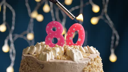 kekler : Birthday cake with 80 number burning by lighter pink candle on blue backgraund. Candles are set on fire. Slow motion and close-up view Stok Video