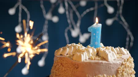 csillagszóró : Birthday cake with 1 number burning blue candle and sparkler on blue backgraund. Slow motion and close-up view