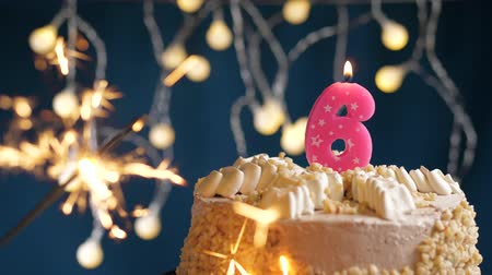 inflar : Birthday cake with 6 number burning pink candle and sparkler on blue backgraund. Slow motion and close-up view